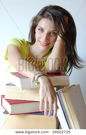 Smiling girl student and pile of books