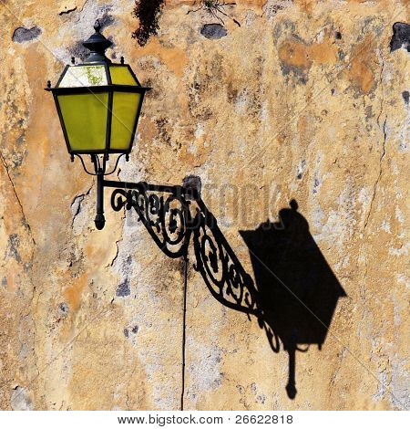 Old yellow lamppost and your shadow on the old wall by scraped plaster