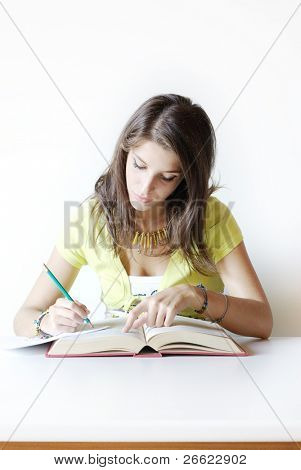 Girl student writes make notes from book
