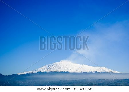 The volcano Etna on a background of the blue sky