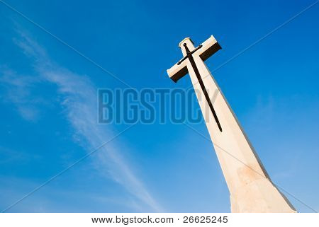 Stone cross in the blue sky