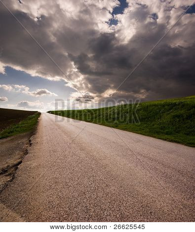 Rural road on horizon stormy clouds