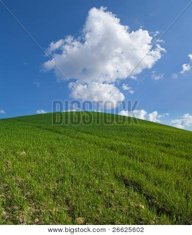 green hill with white clouds