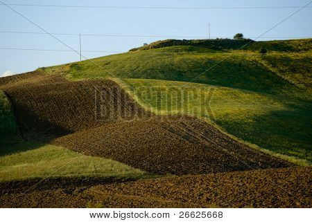 rolling landscaped for red plowed land and green field
