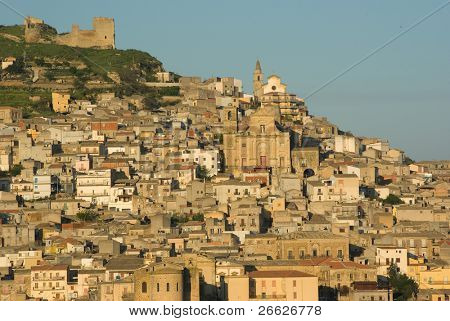 glimpse of the houses and the churches on the hill on which stands the city of Agira in Italy