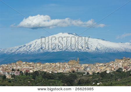 view of dwellings and of the massive cathedral in the village of Regalbuto in Sicily, on background the volcano Etna snowy and big clouds in the blue sky