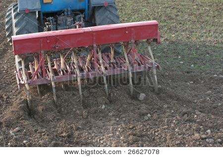 rear closeup view of a articulated tractor with multiple plows that is plowing the earth