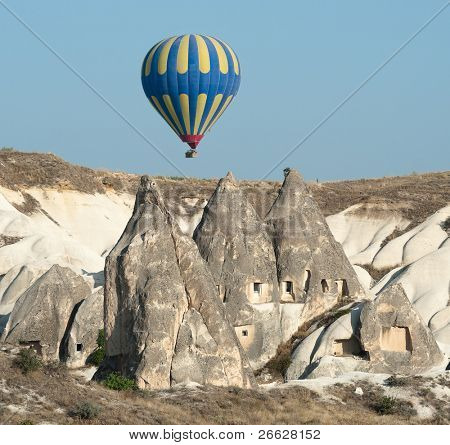 balloon over rock cave houses, typical rock formation in Cappadocia, Turkey