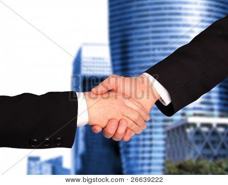 Businessmen Hand shaking with modern building background