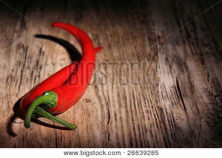 Red hot chili peppers over wooden background
