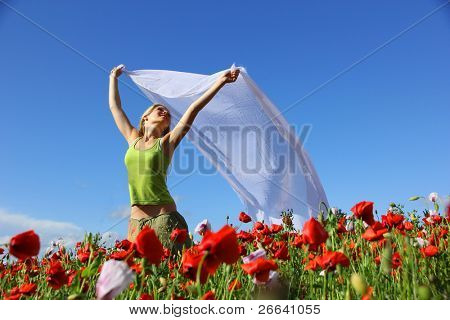 Happy blond girl running in poppy field