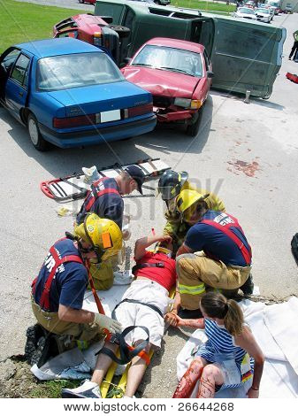 Police officers tend to car crash victims in a staged accident for training purposes