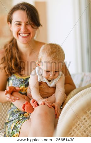 Laughing Mother With Baby Sitting On Knees