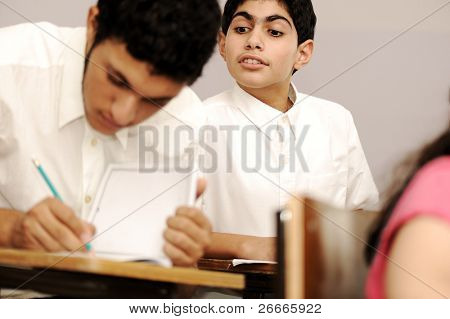 I am lazy but know how to cheat successfully :) Cheating inside the classroom while the exam is present, boy looking above the shoulder of his colleague.