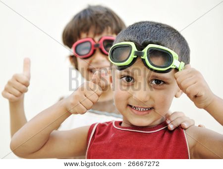 Portrait of two little children friends making funny faces and playing together