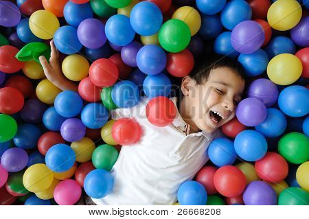 Kid, colors, ball - playing in many colorful balls
