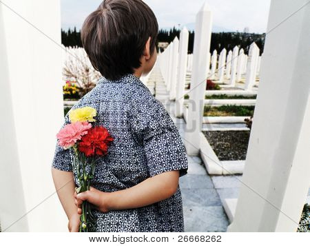 Kid with roses standing on the grave