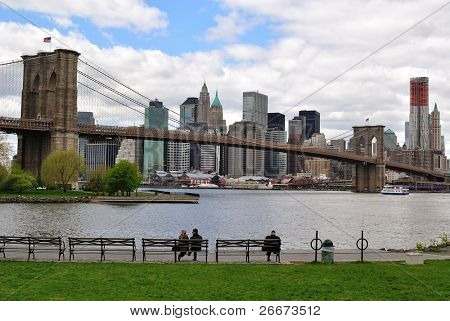 View of Manhattan and Brooklyn Bridge from a Park in Brooklyn with park goers on the benches.
