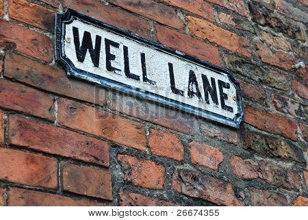 """Señal de tráfico en una lectura de pared de ladrillo """"lane bien"""""""