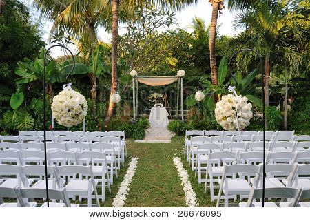 A flower bouquet with roses in front of rows of chairs at a wedding ceremony