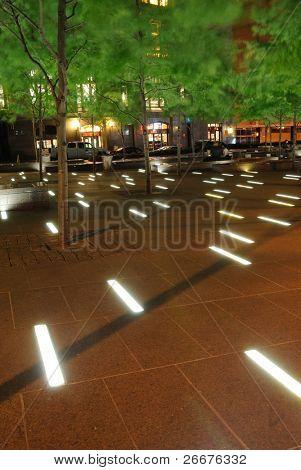 Light floor in Zuccotti Park in lower Manhattan at night in New York, New York.