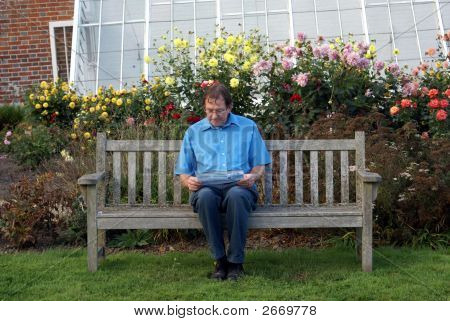 Man Reading Sitting On A Wooden Bench In Front Of A Greenhouse
