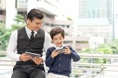 Father And Son Playing Game Smart Phone Together On Business District Urban, Dad And Son Happy Famil poster