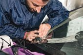 Close Up Automobile Glazier Worker Fixing And Repair Windscreen Or Windshield Of A Car In Auto Servi poster