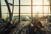 Empty Chairs In The Departure Hall At Airport With Airplane Taking Off At Sunset. Travel And Transpo poster