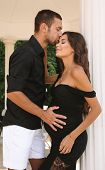 Gorgeous Pregnant Woman With Dark Hair In Elegant Dress Posing With Her Handsome Husband poster