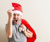 Senior man wearing christmas santa claus hat annoyed and frustrated shouting with anger, crazy and y poster
