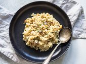 Italian Risotto With Porcini Mushrooms And Fresh Thyme In A Black Plate On A Gray Background. Homema poster