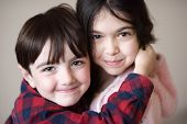 Beautiful Little Smiling Caucasian Boy Embracing Pretty Small Girl With Tenderness poster
