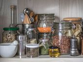Shelf In The Kitchen With Various Jars Of Cereals And Kitchen Tools. Glass Jars With Pasta, Lentils, poster