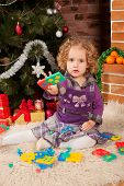 Little girl play near Christmas tree