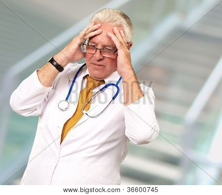 Portrait Of A Senior Doctor Holding His Head, Indoor