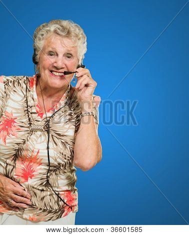 Portrait Of Cheerful Senior Woman With Telephone Headset Isolated Over Colored Background
