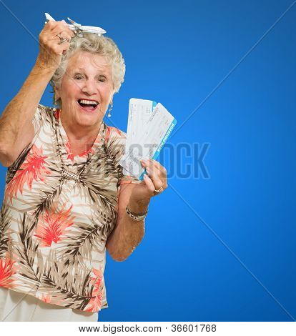 Portrait Of Happy Senior Woman Holding Plane Toy And Journey Tickets Isolated Over Blue Background