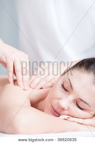 Close-up portrait of relaxing woman having massage on her shoulder