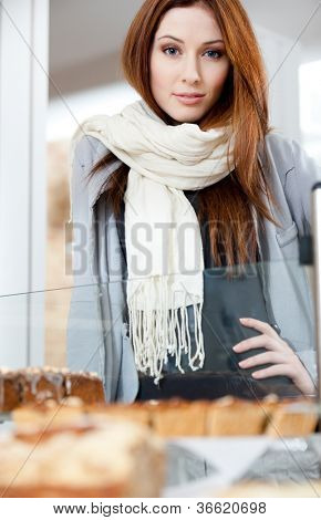 Woman in scarf looking at the bakery window full of different pieces of cakes