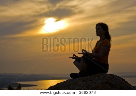 Woman Meditating At The Sunset