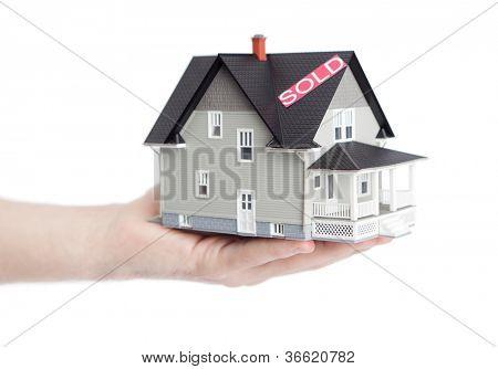 Conceito imóveis - mão segurando o modelo de arquitetura doméstico, isolado