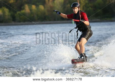 Wakeboarder surfing across the river