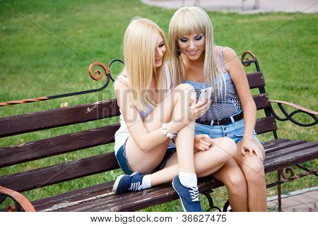 Two girl friends using a modern smartphone