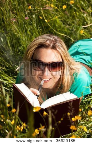 Young Blond Woman With Electric Cigarette  Reading Book