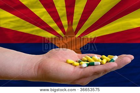 Holding Pills In Hand In Front Of Arizona Us State Flag
