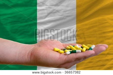 Holding Pills In Hand In Front Of Ireland National Flag