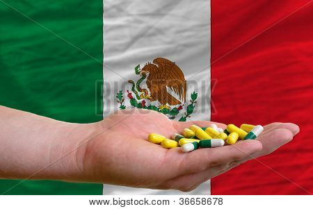 Holding Pills In Hand In Front Of Mexico National Flag