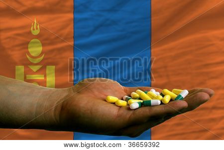 Holding Pills In Hand In Front Of Mongolia National Flag