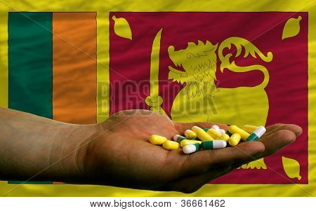 Holding Pills In Hand In Front Of Sri Lanka National Flag